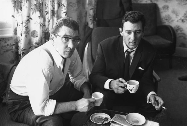 London gangsters Ronnie and Reggie Kray at home having a cup of tea. They had just spent 36 hours being questioned by the police about the murder of George Cornell. (Photo by William Lovelace/Getty Images)